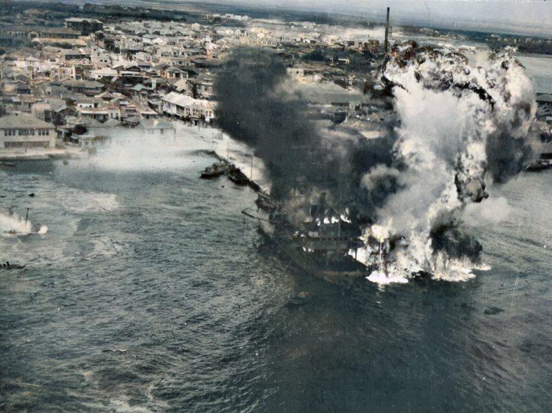 1945年4月4日,美軍B-25J超低空突襲澎湖馬公港。第三棧橋東側的800噸級「第二近油丸」劇烈爆炸(照片中被火焰濃煙遮蓋處),隨後火勢蔓延到西側1,565噸級的「寶嶺丸」上。 圖/Fold3;廖英雁編修。