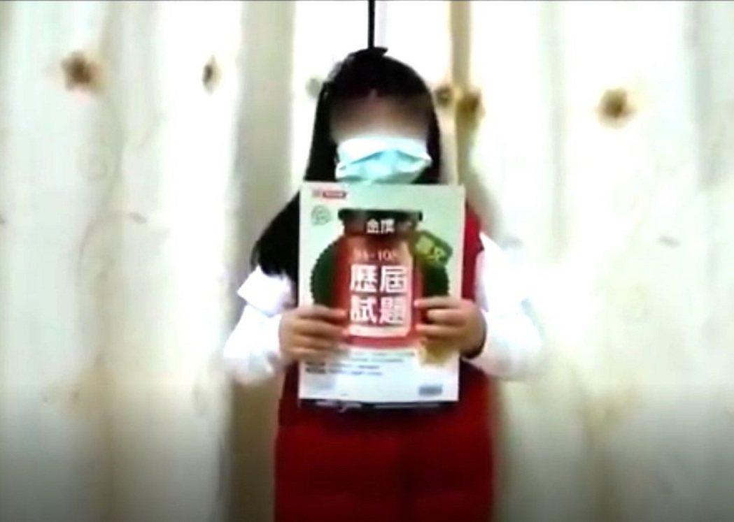 小一女童舉著國三哥哥的課本,擔心哥哥趕不上會考。圖/擷取自影片