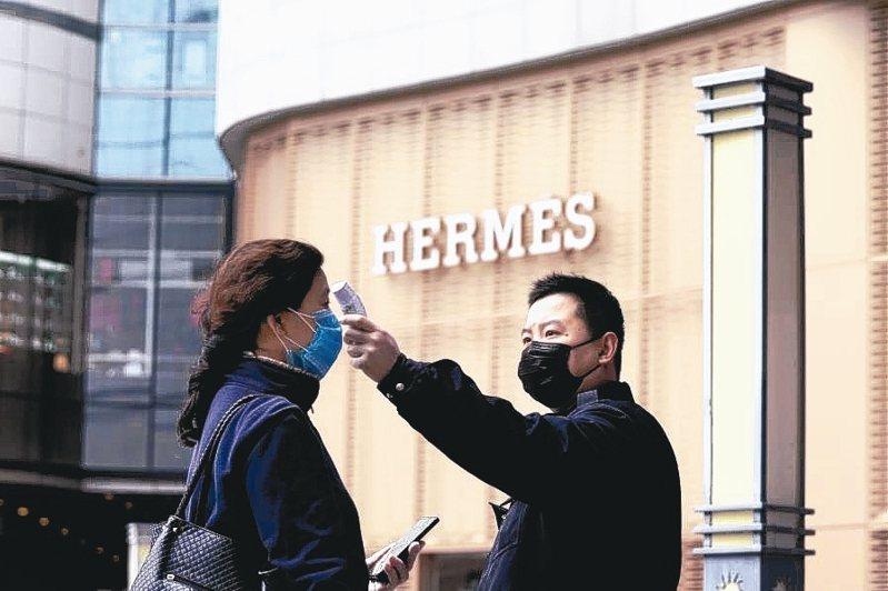 大陸第1季奢侈品銷售額將大減40%。圖為湖北武漢民眾要進入購物中心前量測體溫。 路透
