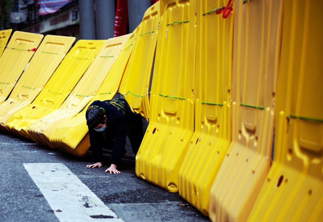 圖為武漢的小區封鎖管理,雖然8日零時起已經解除封城、開放離漢通道出入,但武漢里的...