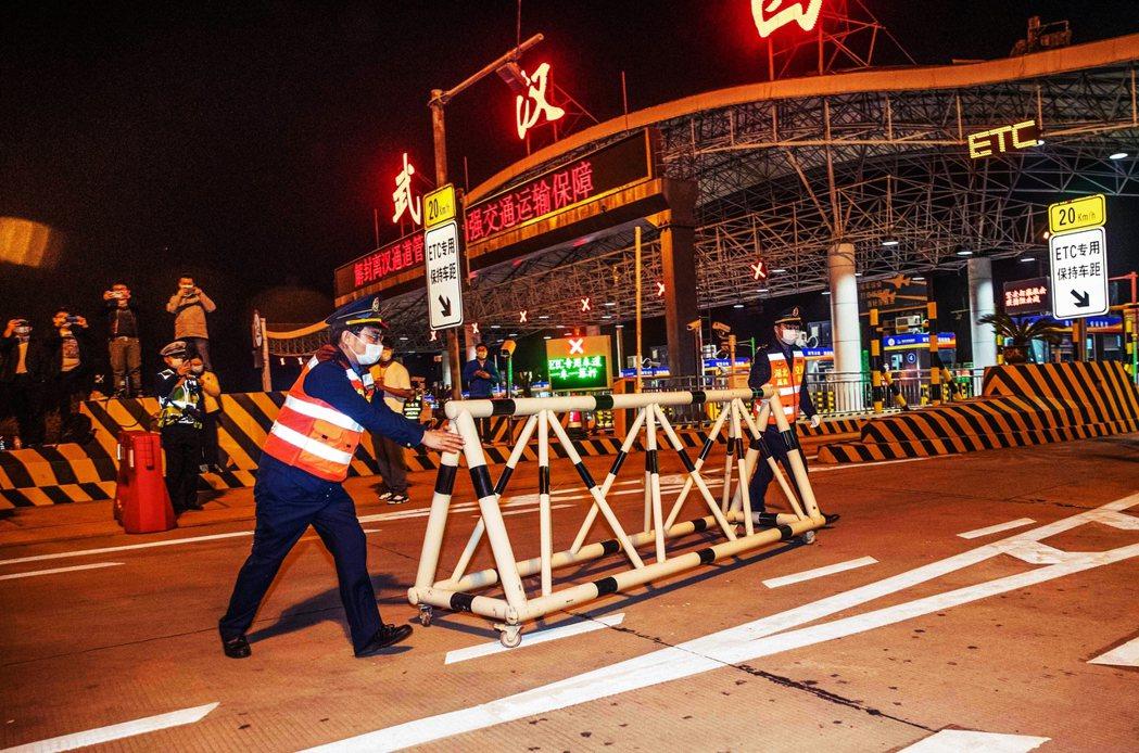 圖為武漢西收費站,8日零時起正式解除封鎖,站務人員移除柵欄路障,這個歷史象徵性的...