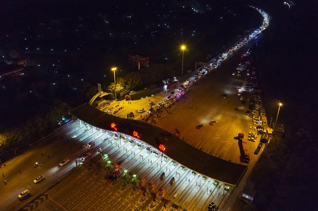 中國官方媒體釋出解封時刻的武漢西收費站照片,當晚許多車流已經準備好要「撤離」武漢...