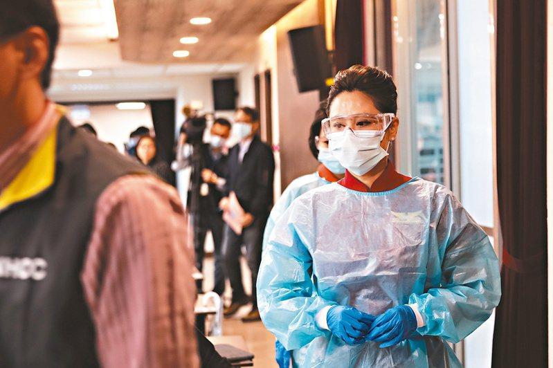 機艙染病風險極高,為避免感染,圖為指揮中心請空服員示範長程班機須穿上防護裝備。目前已有班機出現10名新冠肺炎確診者。  圖/中央流行疫情指揮中心提供