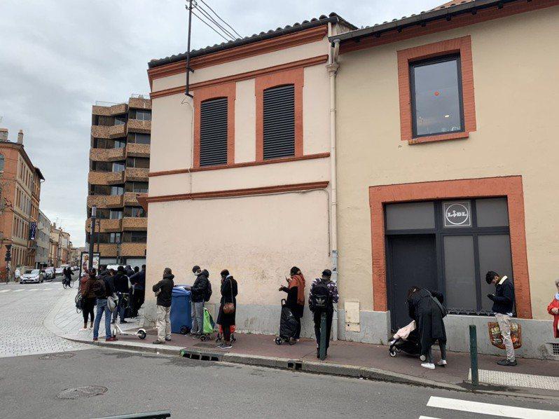 法國宣布封城後,當地家樂福出現排隊人潮,約要排一小時才能進入超市。圖/Charlotte提供