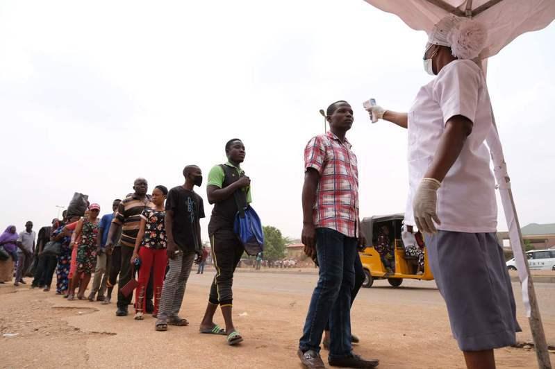 英國樂施會呼籲,採取緊急行動協助貧窮國家。圖為奈及利亞民眾排隊量體溫。法新社