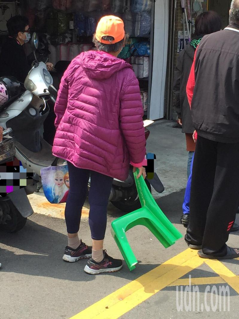 口罩新制今日上路,各地藥局大排長龍,有民眾撐雨傘遮陽,也有民眾自帶椅子排隊等待。記者余采瀅/攝影