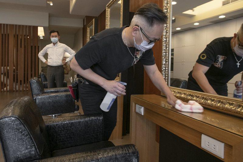 新竹市長林智堅(左)訪視美髮等近距離服務業防疫工作,提醒防疫SOP,包括環境消毒、量體溫、維持室內安全社交距離及梅花座間隔等。圖/市府提供