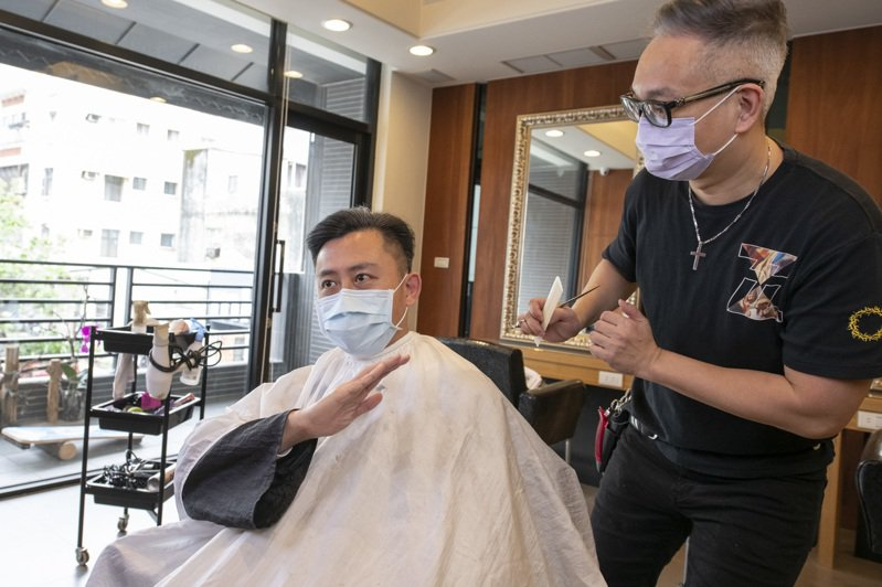新竹市長林智堅(左)剪髮了解美髮等近距離服務業防疫工作,提醒業者防疫SOP,包括環境消毒、量體溫、維持室內安全社交距離及梅花座間隔等。圖/市府提供