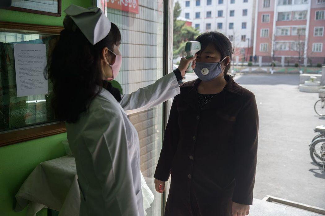 平壤的平川人民醫院入口,有護理人員在量額溫。法新社