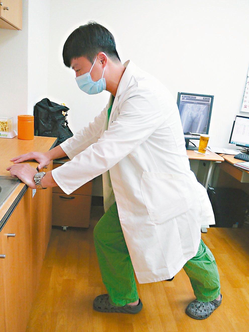 骨科醫師林書樊示範登山前暖身運動,可以扶著牆壁拉筋。 記者徐白櫻/攝影
