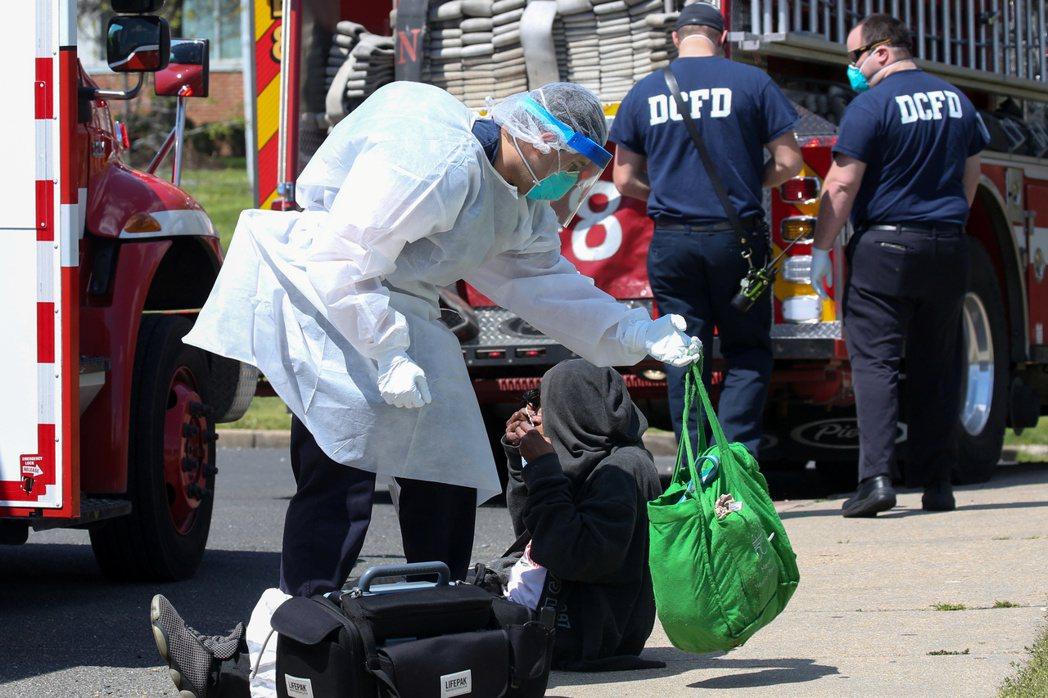 美國華府一名醫護人員穿戴防護裝備,準備協助一名疑似新肺病患就醫。(路透)