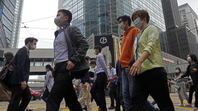 新冠病毒疫情陰影下,走在香港市中心街道的人,都戴上口罩。圖/美聯社