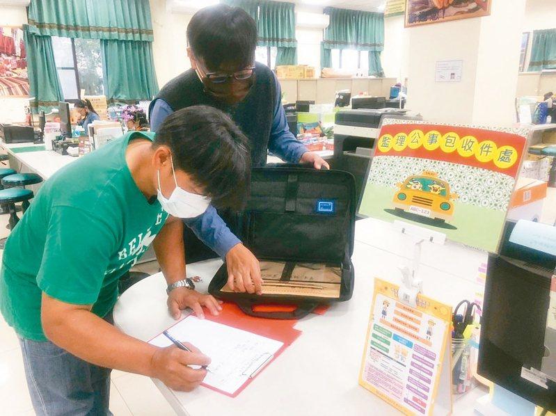 那瑪夏幸福小黃司機朱彥彬簽收「監理公事包」,將當地人換行照的文件與規費,載到旗山監理站。 記者侯俐安/攝影