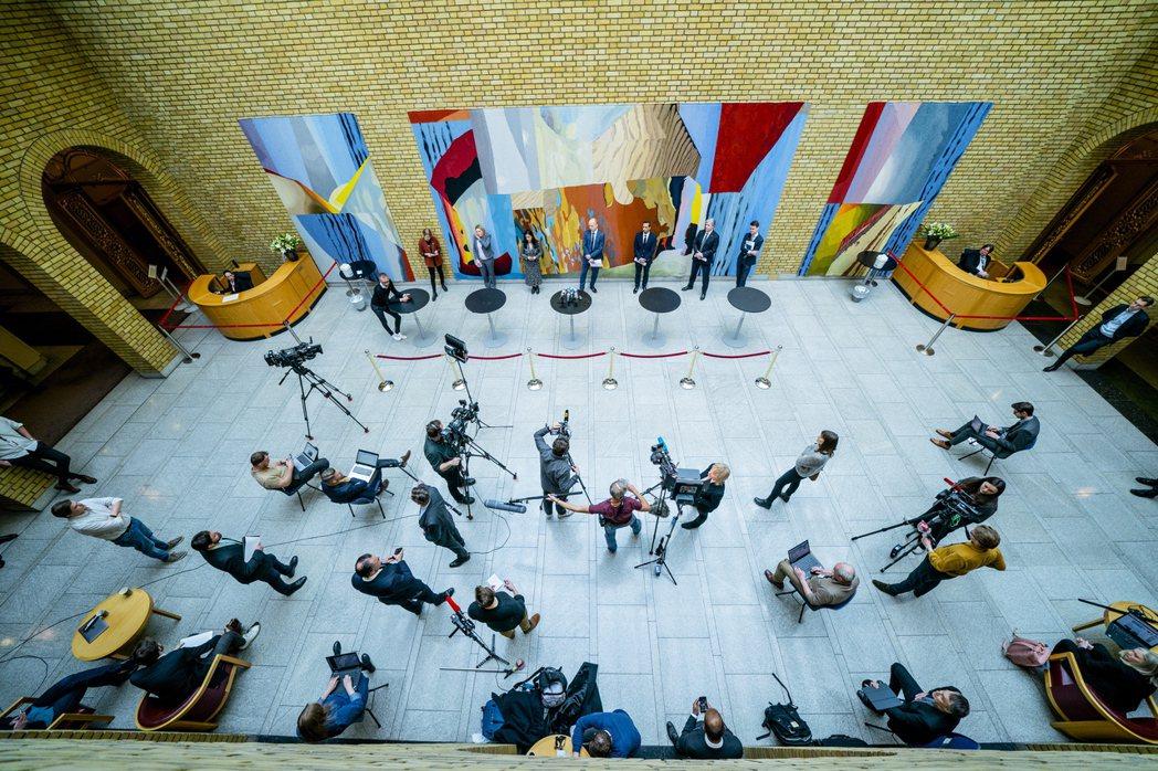 挪威政府舉辦記者會說明第三輪危機計畫,議會成員與記者皆須遵守社交距離。 圖/歐新社