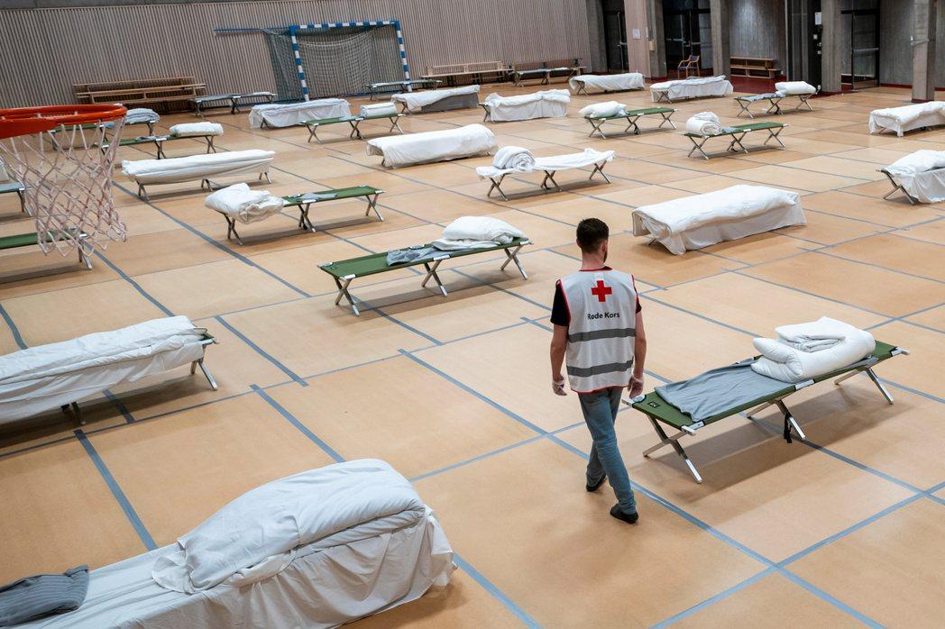 在奧斯陸的一所學校體育館中,提供給無家者的床鋪被設置為符合社交距離,以減少感染風險。 圖/路透社