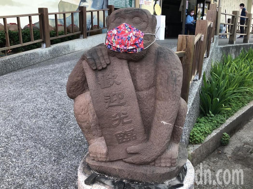 嘉義觀光酒廠2隻守門的石猴,戴上特製的花布口罩,呼籲民眾戴口罩防疫,石猴戴口罩造...