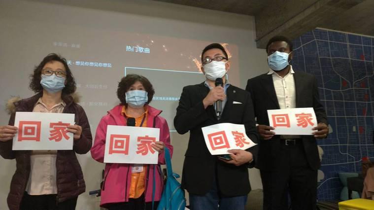 湖北台胞返鄉救援會長徐正文(右二)與三名滯留武漢台胞的家屬,舉著回家的牌子,呼籲...