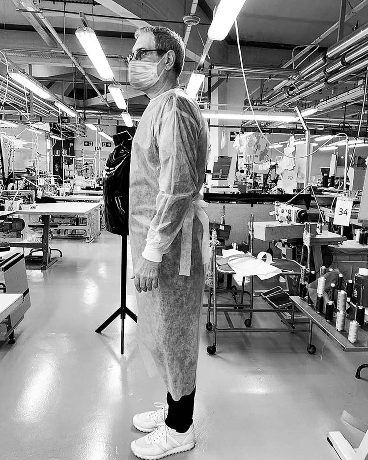 Giorgio Armani也在近日投入防護衣生產,並由工廠人員示範穿戴樣式。圖...