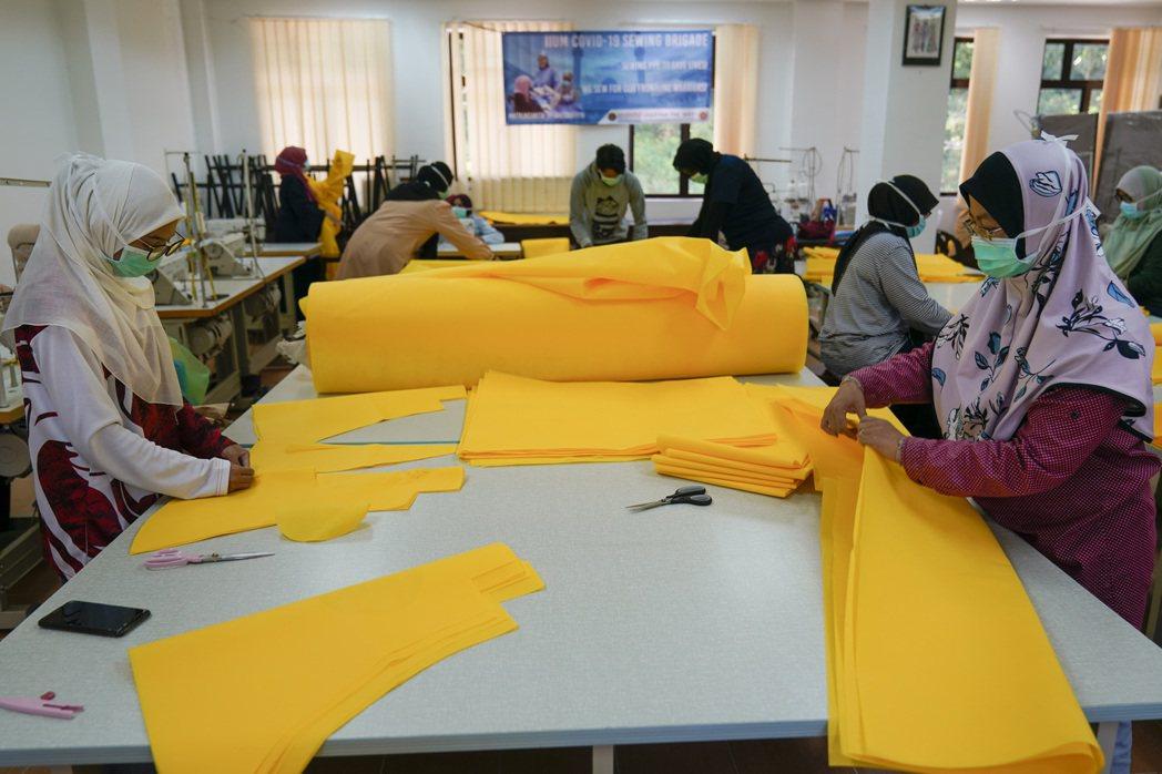 吉隆坡市郊有志工在幫忙製作防護衣。美聯社