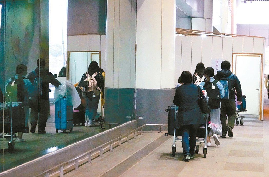 入境旅客有症狀者必須集中檢疫,等待採檢結果。不少旅客在採撿站前排隊等候。本報資料...