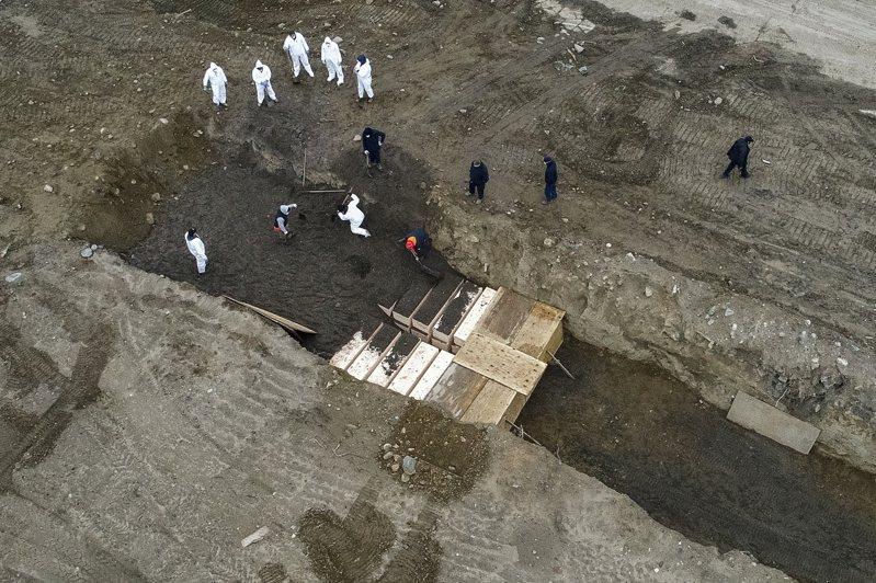 紐約市哈特島的空拍畫面拍到穿防護衣的工作人員挖壕溝集體埋葬幾十具棺木。美聯社