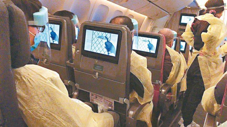 上一批搭乘華航「類包機」的湖北台灣民眾在機上穿著防護服。圖/徐正文提供