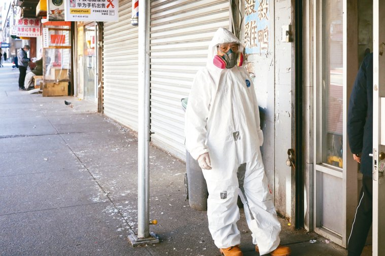 紐約疫情嚴重,在法拉盛華人社區,一位民眾身穿防護服去藥店取藥。 中新社