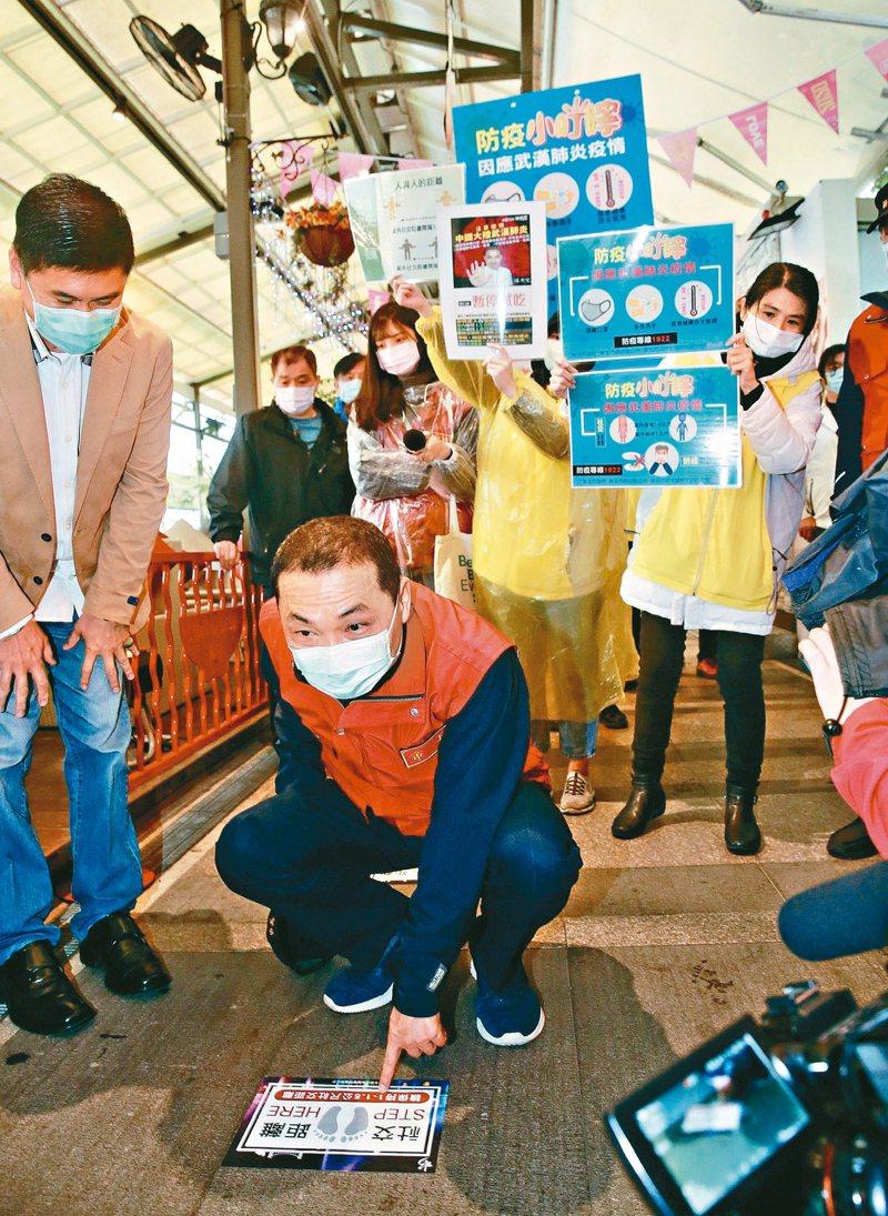 新北市長侯友宜(前蹲者)昨到碧潭視察,並檢視標示社交距離的指示牌。 記者黃義書/攝影