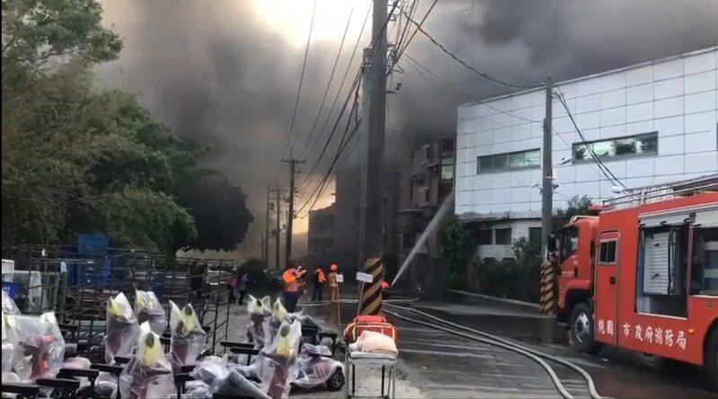 新屋工廠倉庫火警,消防局調派多輛消防車和人員搶救中。記者鄭國樑/翻攝