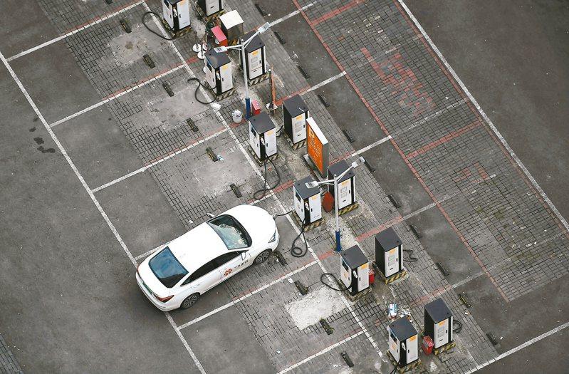 大陸今年預計新增新能源汽車充電樁60萬個。圖為重慶大渡口一停車場,一新能源車輛正在充電樁處充電。 中新社