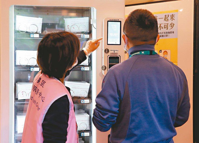 勞動部安心即時上工計畫工作內容以「防疫」為最大宗,圖為台北市信義區公所人員協助使用口罩販賣機。 記者余承翰/攝影