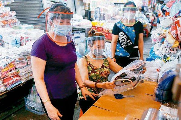 胡志明市市場攤販戴起塑膠面罩。 路透