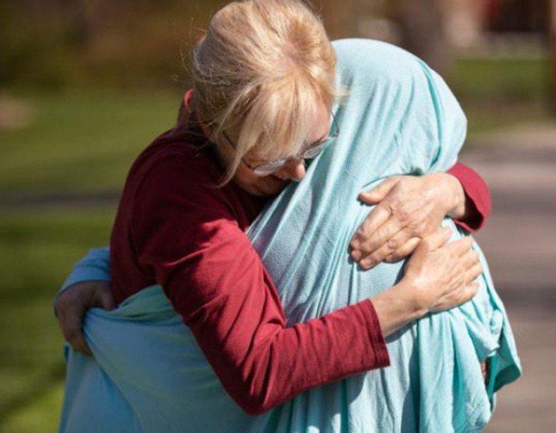 雪洛‧諾頓用床單包住,給女兒凱西‧柯爾一個大擁抱。(截頻自CNN)