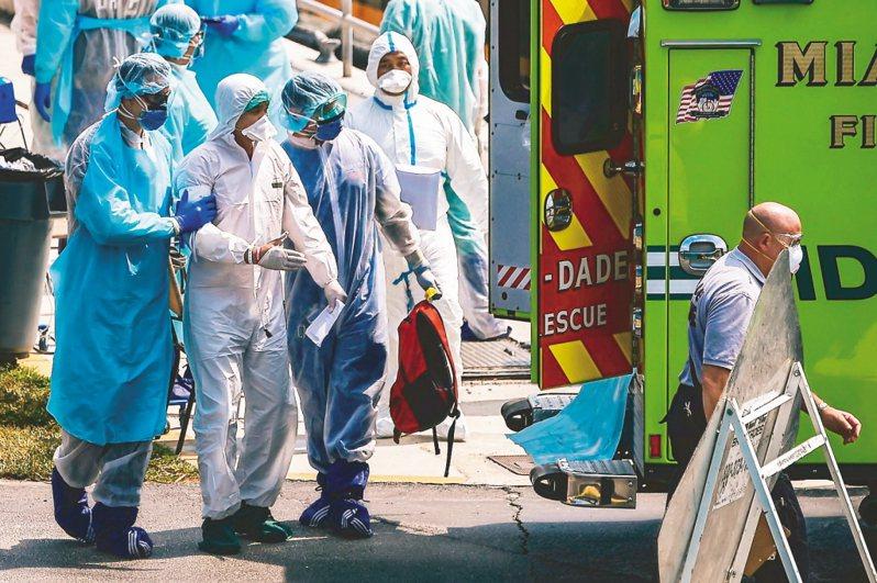 圖為美國海岸巡防隊26日在邁阿密協助有肺炎等呼吸道症狀的郵輪船員就醫。 法新社
