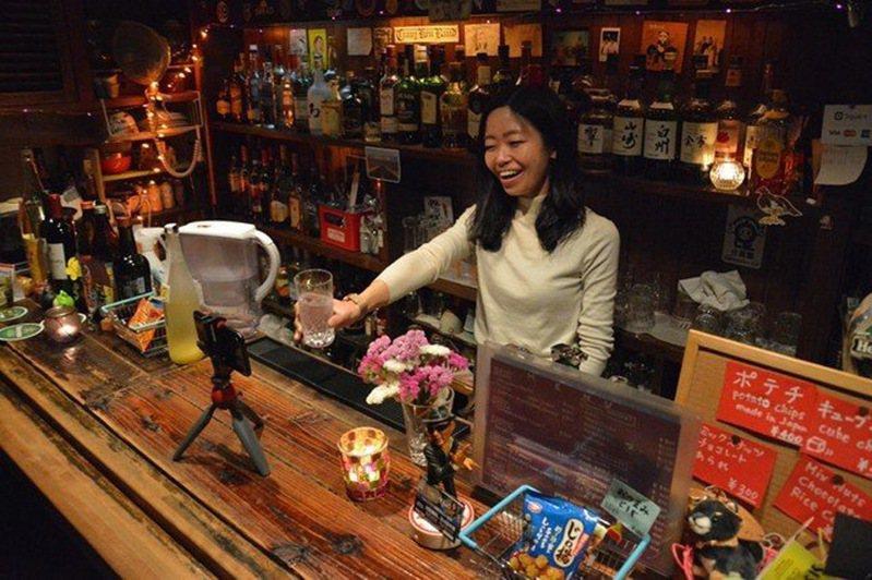 紙月吧的老闆娘,透過鏡頭與客人乾杯對飲。圖/Maidonanews