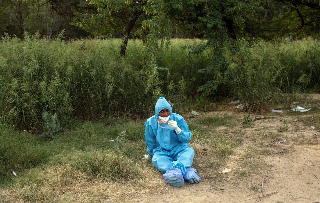 圖為新德里一名醫護人員,累癱坐在草地上就地休息。 圖/路透社