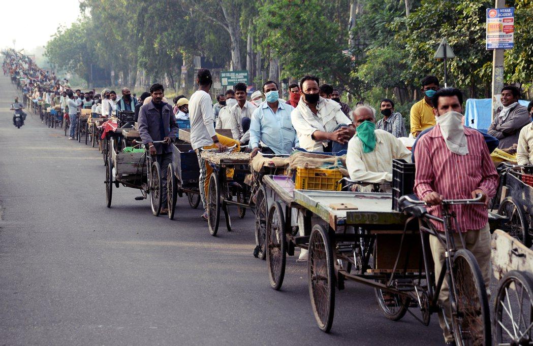 印度封城至少將延長至5月3日。圖為封城期間,排隊等待進入批發市場採買物資的印度民...