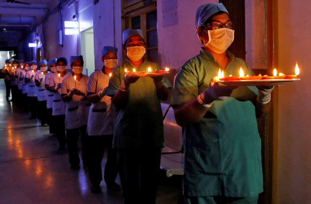 圖為印度醫護人員點燈,以示團結抗疫。 圖/路透社