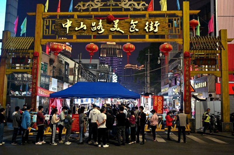 民眾需出示健康碼才能進入夜市,攝於4月10日,廣西南寧市中山路美食街。 圖/中新社