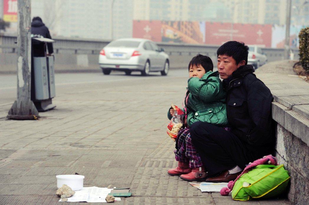 2010年,北京街頭一名父親正在送養女兒,地上擺著證件資料,徵求好心人「有價收養...