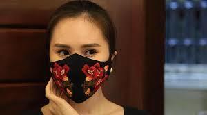 越南時尚設計師華度權以精湛的手工技巧在口罩上繡出細緻花朵圖案。(photo by YouTube)