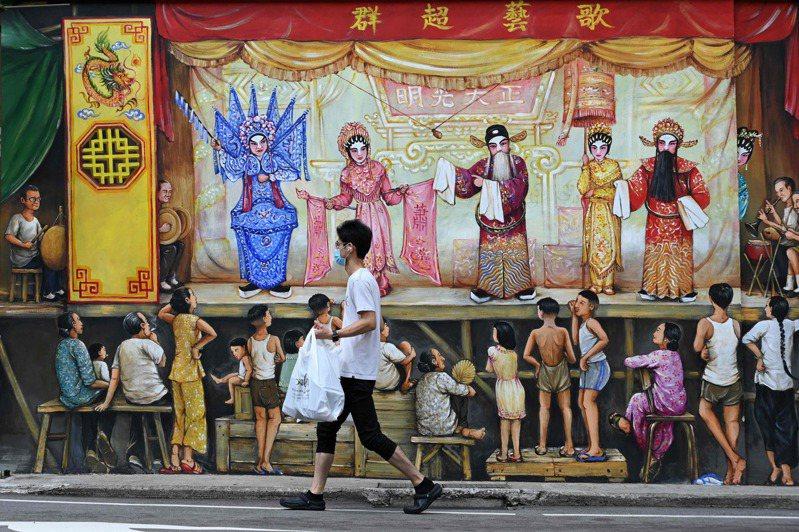 新加坡唐人街有男子戴口罩帶外賣路過一幅壁畫。法新社