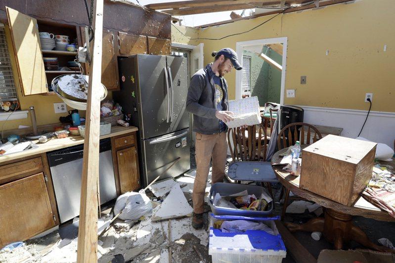 圖為田納西州一名男子在被毀的住家內收拾完好的物品。(美聯社)