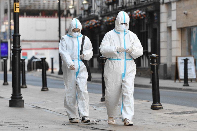 一對穿著防護衣的夫婦走在英國曼徹斯特空盪盪的街頭。 法新社