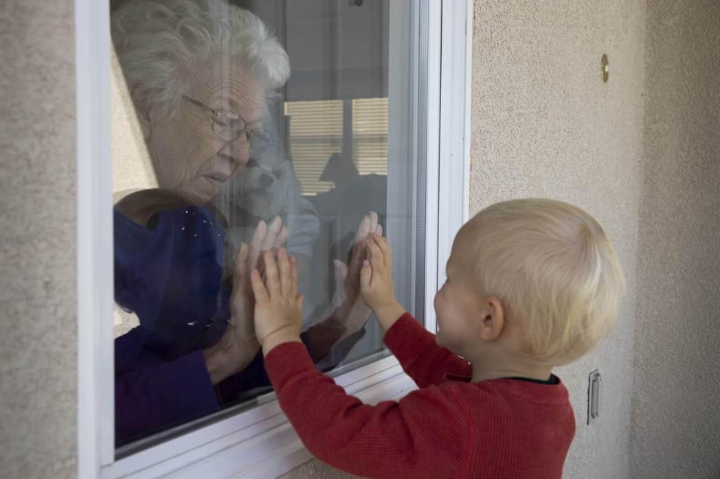 圖為美國加州一名老人,隔窗與鄰居的小弟弟打招呼。 圖/法新社
