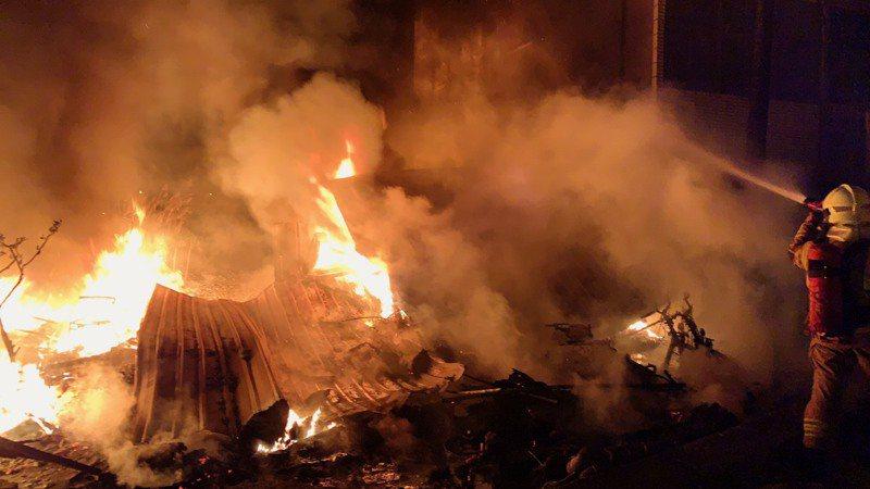 台南北門蘆竹溝暗夜惡火竄出,2樓倉庫全面燃燒,消防隊員忙灌救。記者謝進盛/翻攝