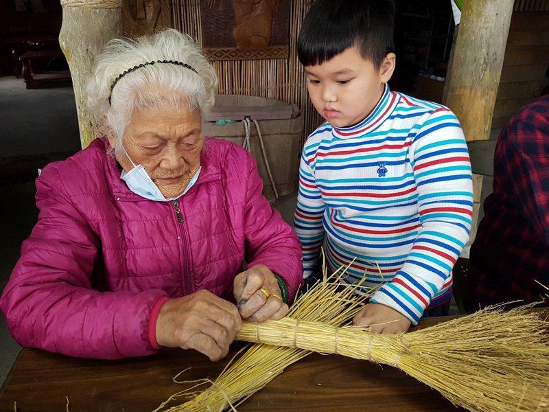 馬太鞍部落耆老吳連妹阿嬤(左)利用cilipeday稻穀指導小朋友製作掃帚圖/花蓮農改場提供