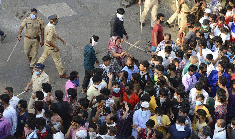 印度警察14日在孟買驅散上街抗議為疫情延長封鎖的民眾。  美聯社