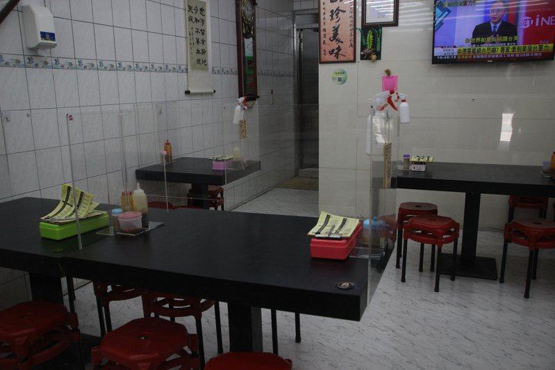 疫情期間,員林市一家鴨肉飯店家在桌上加裝壓克力隔離板。記者林敬家/攝影