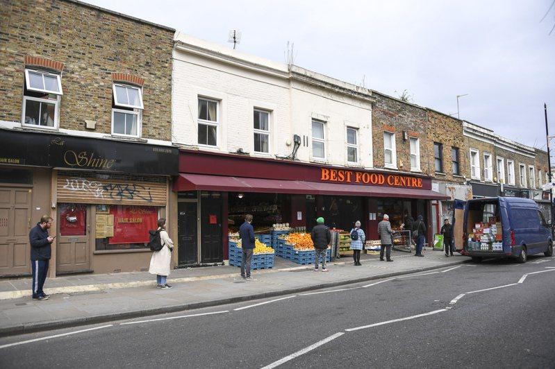 英國民眾日前在倫敦一間雜貨店外保持社交距離等待購物。 美聯社